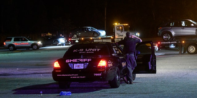 A Clayton County Sheriff's Deputy stands watch over a parking lot at Mt. Zion High School as three cars are towed away as part of an investigation into a fatal shooting Friday, May 18, 2018, in Jonesboro, Ga. One person was killed and another wounded.
