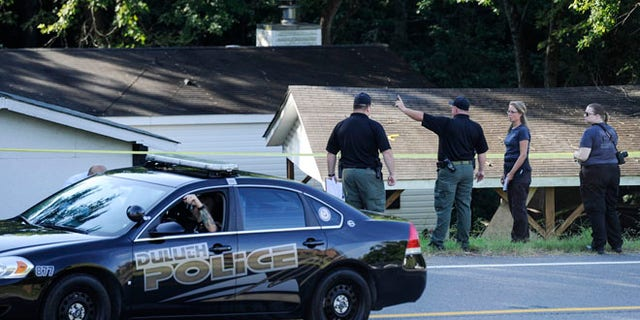 Law enforcement investigate the scene of a shooting at a home in Suwanee, Ga.,  Wednesday, July 22, 2015.  Officers initially found three people dead and two wounded, including the suspect, Forsyth County sheriff's officials said. The wounded were taken to hospitals, where one died, Deputy Robin Regan said. But it wasn't clear whether that was the suspect or the other person. (AP Photo/John Amis)