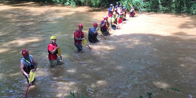 Rescue crews walk down Barber Creek in hopes of locating two teenager boys were were swept away on Friday.