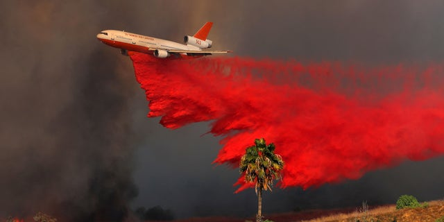A DC-10 aircraft drops fire retardant on a wind driven wildfire in California.