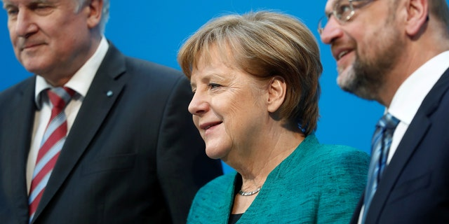 Christian Democratic Union leader and German Chancellor Angela Merkel, Christian Social Union leader Horst Seehofer and Social Democratic Party leader Martin Schulz pose after a statement in Berlin, Germany, Feb. 7, 2018.