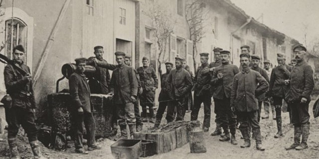 Captured German prisoners draw water from a well for their mess hall in Pierrefitte-sur-Aire, France.