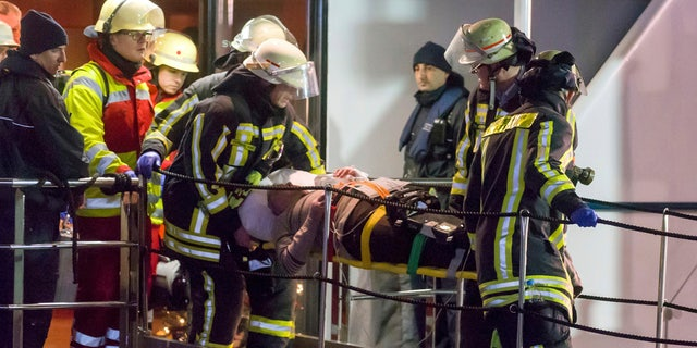 In this Dec, 26, 2017 photo, rescuers carry an injured passenger off a damaged tourist ship in Duisburg, Germany.