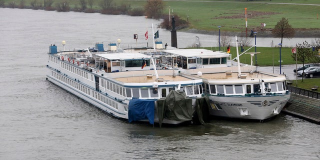 A tourist ship, left, is tied up at another ship in Duisburg, Germany, Wednesday, Dec. 27, 2017.