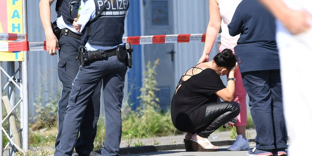 A visitor, center, waits to be questioned by police near a discotheque in Constance, at Lake Constance, Germany, Sunday, July 30, 2017.