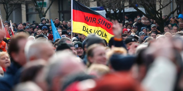 People hold German flags as they attend a demonstration against migrants in Cottbus on Feb. 3.