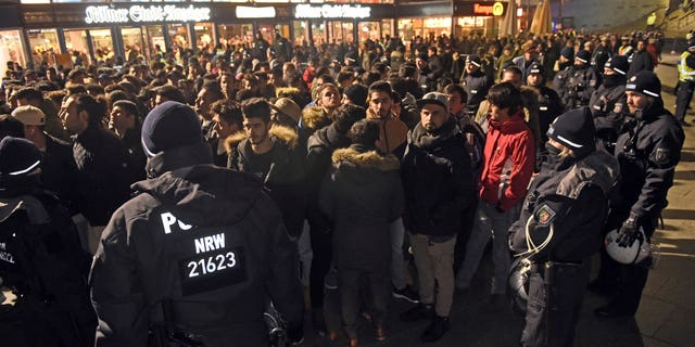 Police officers surround a group of men in front of the Cologne, western Germany, main station, Saturday, Dec. 31, 2016, where a string of robberies and sexual assaults last year that were blamed largely on migrants from North Africa prompted nationwide outrage. (Henning Kaiser/dpa via AP)