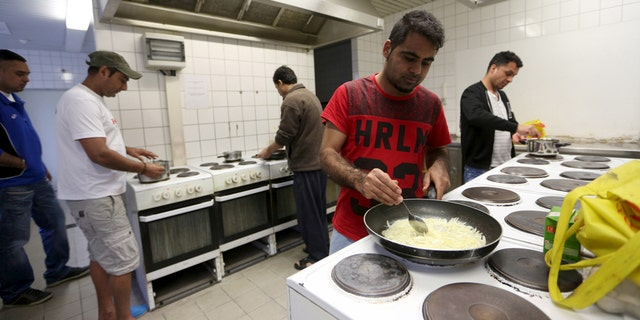 """March 24, 2016: Migrants cook in the kitchen of the accommodation for migrants """"Spree Hotel"""" in Bautzen, Germany."""