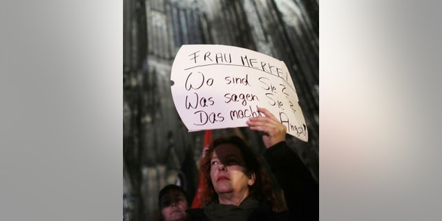 """A woman protests against sexism outside the cathedral in Cologne, Germany, Tuesday Jan. 5, 2016. Poster reads """" Mrs. Merkel. Where are you? What do you say? It's scary."""" (Associated Press)"""