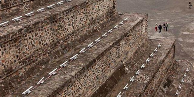 Tourists walk toward the Pyramid of the Moon in Teotihuacan, Mexico.