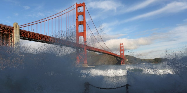 Waves crash against a sea wall in San Francisco Bay beneath the Golden Gate Bridge in San Francisco, California December 16, 2014.