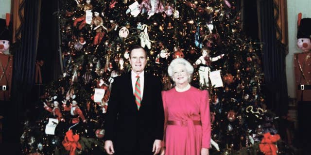 President%20George%20Bush%20and%20Mrs.%20Barbara%20Bush%20pose%20in%20front%20of%20the%20White%20House%20Christmas%20tree%20in%20the%20White%20House%20Blue%20Room%20on%20Dec.%2019%2C%201990.%0A