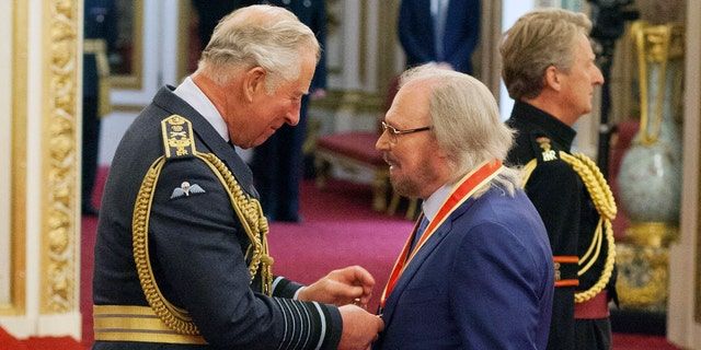 Singer and songwriter Barry Gibb talks with Prince Charles, left, during an Investiture ceremony to award a knighthood to Gibb, at Buckingham Palace in London, Tuesday June 26, 2018.