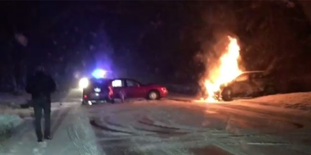 Ralph Gilles approaches the scene of an accident after using his Jeep to push a flaming SUV away from a car with passengers stuck inside.
