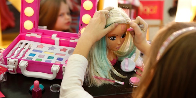 A young girl paints the face of a doll by the company Simba during the press preview of the 66th International Toy Fair in Nuremberg January 27, 2015. (REUTERS/Michaela Rehle)