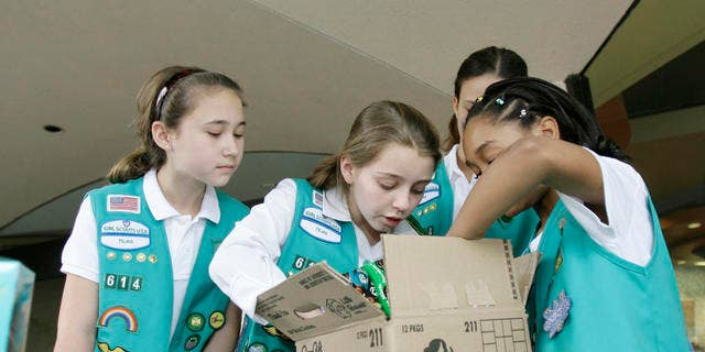 File Photo: Girl Scouts sort through a case of Girl Scout cookies, Friday, Feb. 23, 2007, in Dallas.
