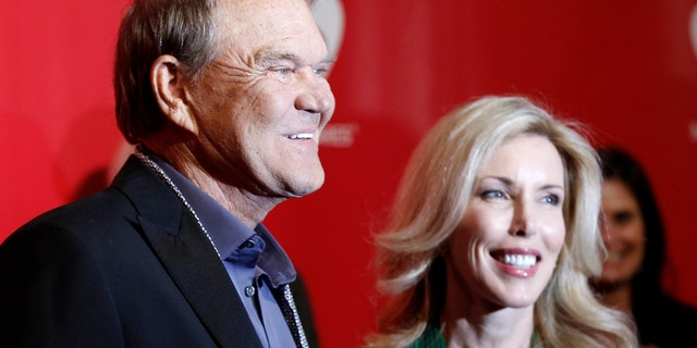 Musician Glen Campbell (L) and wife Kim Woollen pose at the 2012 MusiCares Person of the Year tribute honoring Paul McCartney in Los Angeles, February 10, 2012. REUTERS/Danny Moloshok.