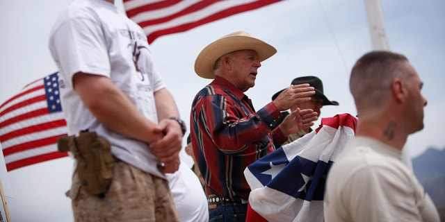 Rancher Cliven Bundy, flanked by armed supporters, speaks at a protest camp near Bunkerville, Nevada, on April 18, 2014.