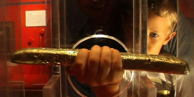 A boy picks up the gold bar in a photo taken before the theft of the rare artifact.