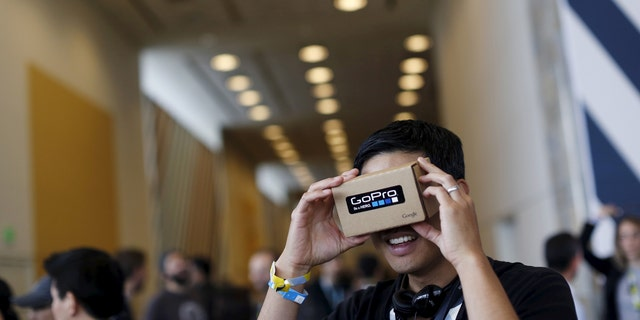 "File photo: A conference attendee looks through ""Cardboard,"" a viewer that enables the user to view content from a smart phone in 3D, during the Google I/O developers conference in San Francisco, California May 28, 2015. (REUTERS/Robert Galbraith)"