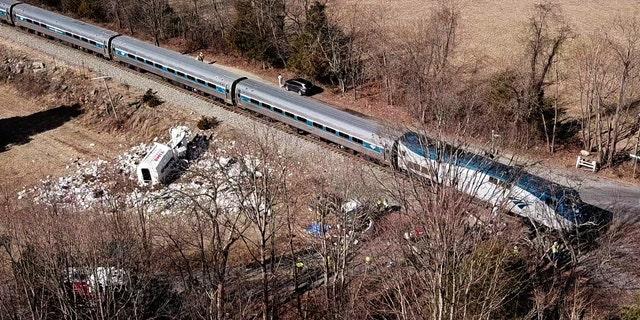 The wreckage of a garbage truck lies beside an Amtrak passenger train