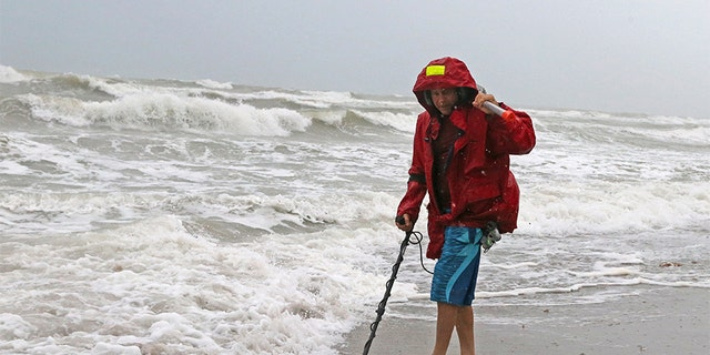Local resident Mike Squillace looks for metal at Dania Beach, Fla., as Tropical Storm Gordon passes by South Florida with wind gusts and heavy rainfall on Monday.