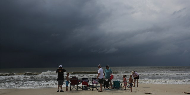 A family watches the first rains clouds from Tropical Storm Gordon roll in on Tuesday in Dauphin Island, Ala.