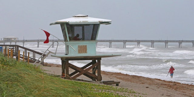 A view of the lifeguard tower while local resident Mike Squillace looking for metal at Dania Beach, Fla., as Tropical Storm Gordon pass by South Florida.