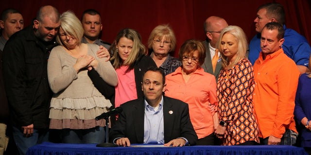 Kentucky Gov. Matt Bevin, seated, signs a prayer proclamation as Marshall County High School reopened its doors in Benton, Ky., Jan. 26, 2018.