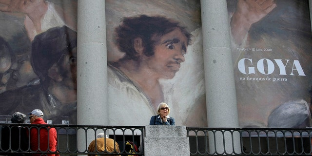 File photo - People sit in front of a banner announcing an exhibition by Spanish legendary artist Francisco Goya at Madrid's El Prado museum in Madrid April 15, 2008. (REUTERS/Andrea Comas)