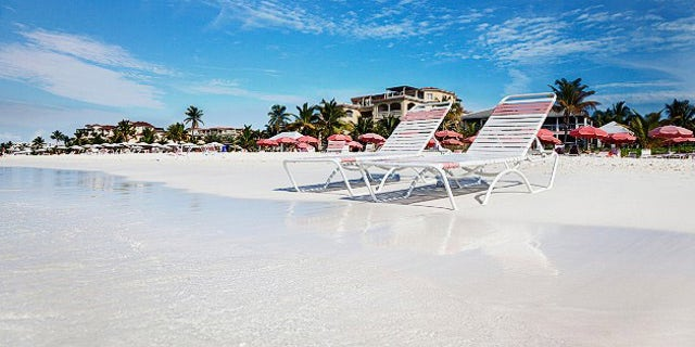 Beach chaises at water's edge on the soft white sands of Grace Bay Beach, Turks & Caicos