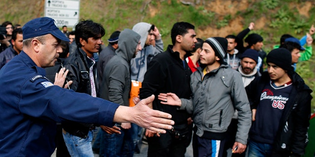 March 28, 2016: A police officer blocks migrants near the Evzoni border crossing, Greece.
