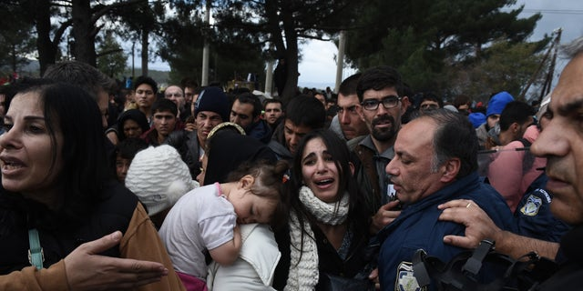 A woman cries as refugees scuffle with the Greek police in their effort to reach the borderline with Macedonia, near the Greek village of Idomeni, Sunday, Nov. 22, 2015. (AP)