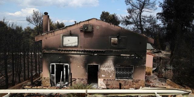 A burned house is seen in Agios Andreas, east of Athens.
