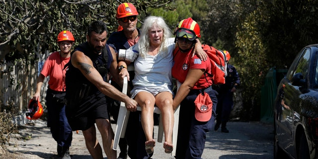 Members of a rescue team carry an injured woman in Mati, east of Athens.