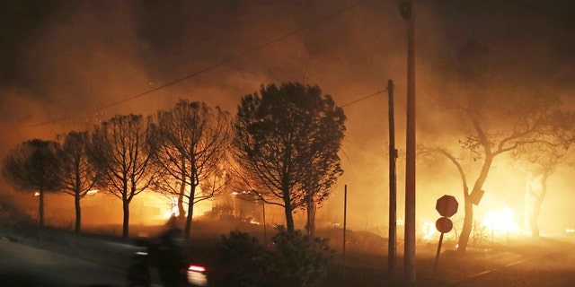 Buildings burn in the town of Mati, east of Athens, Monday, July 23, 2018.