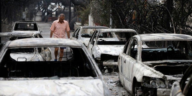 A man passes burned cars in Mati, east of Athens, Tuesday, July 24, 2018.