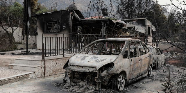 Burnt cars are still in the driveways of destroyed house in Kineta village, west of Athens, Tuesday, July 24, 2018.