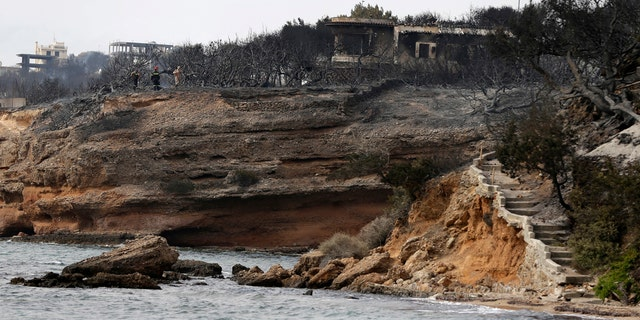 Twin wildfires raging through popular seaside areas near the Greek capital have torched homes, cars and forests and killed at least 60 people, authorities said