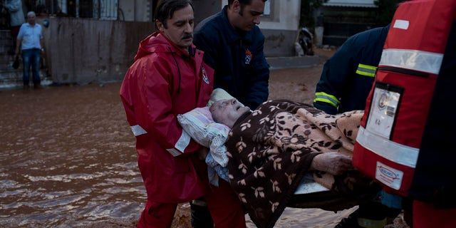 Red cross personel and firemen carry an elderly man to the ambulance in the municipality of Mandra western Athens, on Wednesday, Nov. 15, 2017. Flash floods in the Greek capital's western outskirts Wednesday turned roads into raging torrents of mud and debris, killing at least nine people, inundating homes and businesses and knocking out a section of a highway. (AP Photo/Petros Giannakouris)