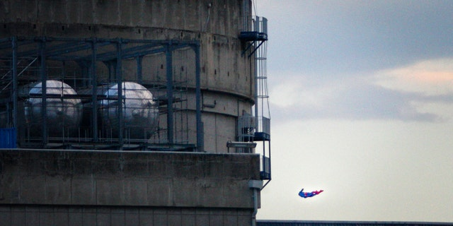 In this photo released by Greenpeace, a drone resembling the character of Superman flies over the nuclear power plant of Le Bugey, central, France, Tuesday, July 3, 2018.