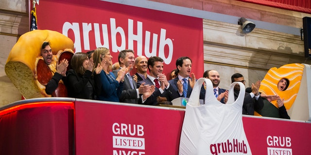 File photo: GrubHub CEO Matt Maloney (C) applauds after ringing the opening bell before the company's IPO on the floor of the New York Stock Exchange in New York April 4, 2014. (REUTERS/Lucas Jackson)