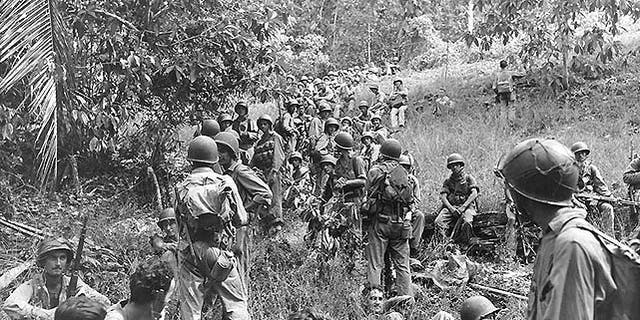 U.S. Marines rest in a field on Guadalcanal, circa August-December 1942. Most of these Marines are armed with M1903 bolt-action rifles and carry M1905 bayonets and USMC 1941 type packs. (U.S. Navy/National Archives)