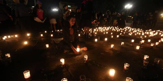 Members of the Family Survivors Foundation attend a candlelight vigil in honor of the victims of a fire that broke out at a children's shelter in Guatemala, March 8, 2017.