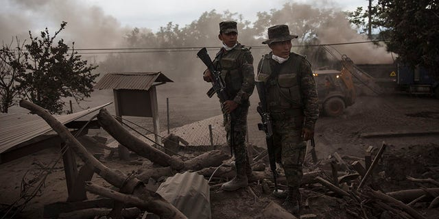 June 6, 2018: Soldiers stand guard outside a destroyed home in the disaster zone covered in volcanic ash in the El Rodeo hamlet of Escuintla, Guatemala.