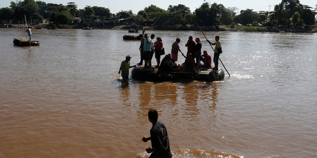 People arrive on a raft after crossing the Suchiate river, a natural border between Mexico and Guatemala.
