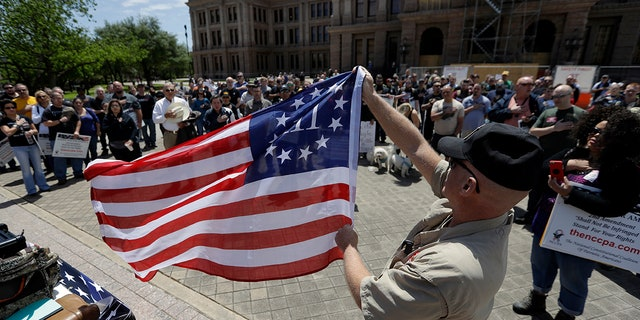 A man holding a 3% flag as a group recited the pledge during a pro gun-rights rally at the state capitol in Austin, Texas.