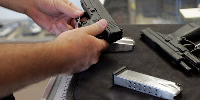 A customer inspects a 9mm handgun at Rink's Gun and Sport in the Chicago, suburb of Lockport, Illinois.