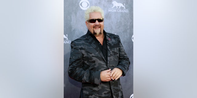 Celebrity chef Guy Fieri arrives at the 49th Annual Academy of Country Music Awards in Las Vegas, Nevada April 6, 2014.    REUTERS/Steve Marcus (UNITED STATES  - Tags: ENTERTAINMENT FOOD)    (ACMAWARDS-ARRIVALS)  - RTR3K6OS