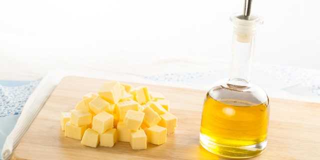 Olive oil in bottle and butter cubes on food preparation surface.